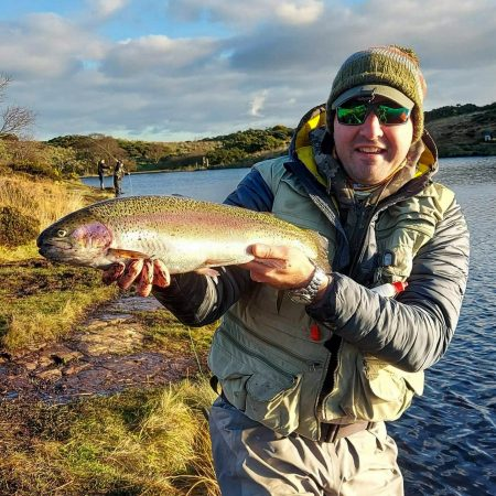 Arden Pollock with a cracking rainbow trout caught from a small water