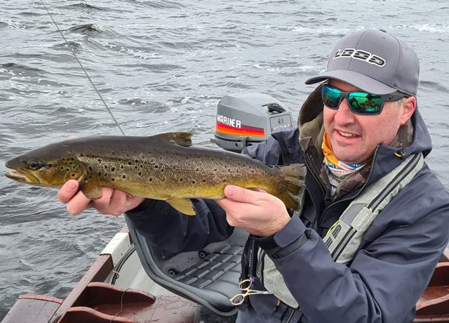 Man holding up brown trout